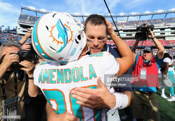 Tom Brady of the New England Patriots hugs Danny Amendola of the Miami Dolphins after the New England Patriots defeated the Miami Dolphins 387 at...