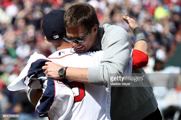 Tom Brady of the New England Patriots hugs Dustin Pedroia of the Boston Red Sox after throwing out the first pitch before the opening day game...