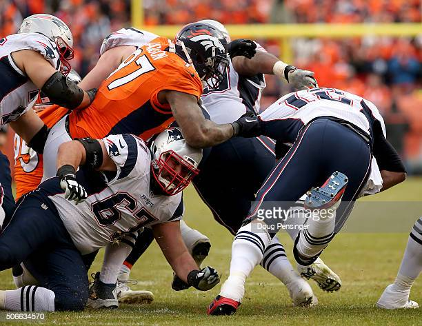 Tom Brady of the New England Patriots is brought down by Malik Jackson of the Denver Broncos in the second half in the AFC Championship game at...