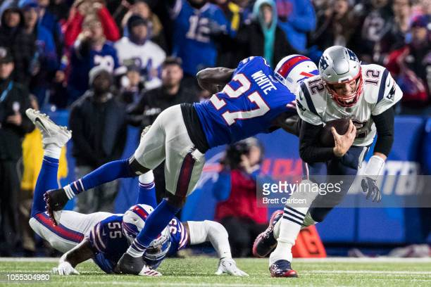 Tom Brady of the New England Patriots is brought down by Tre'Davious White of the Buffalo Bills on a quarterback keeper during the first quarter at...
