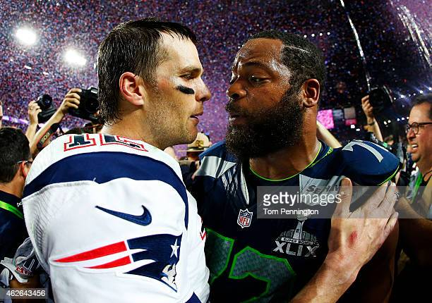 Tom Brady of the New England Patriots is congratulated by Michael Bennett of the Seattle Seahawks after Super Bowl XLIX at University of Phoenix...