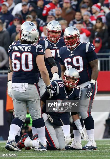 Tom Brady of the New England Patriots is helped up by teammates in the second half during the AFC Championship Game against the Jacksonville Jaguars...