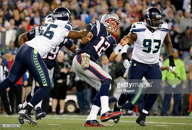 Tom Brady of the New England Patriots is hit as he passes by Cliff Avril of the Seattle Seahawks during the second quarter of a game at Gillette...