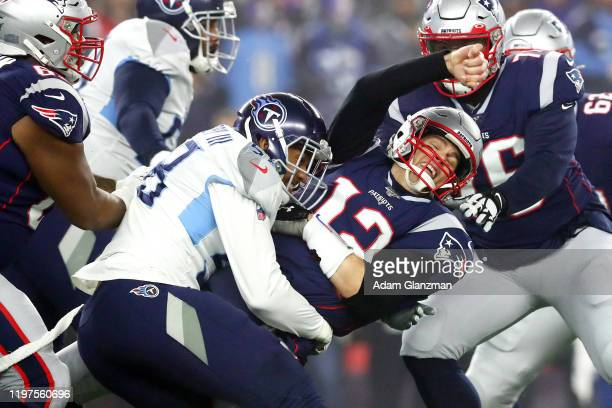 Tom Brady of the New England Patriots is hit as he throws the ball by Harold Landry of the Tennessee Titans in the first quarter of the AFC Wild Card...