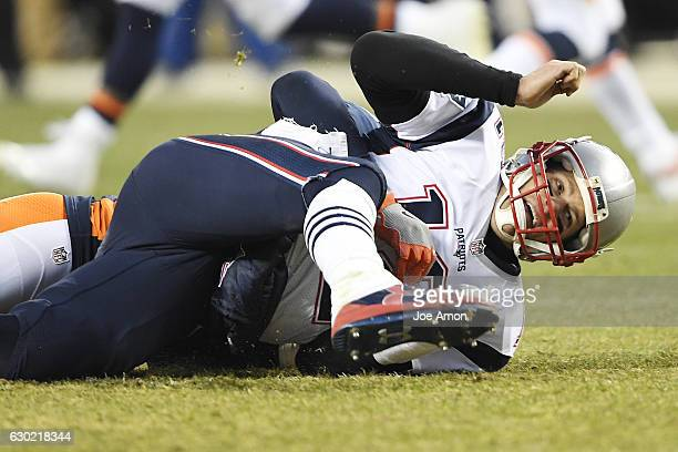 Tom Brady of the New England Patriots is knocked down by Shane Ray of the Denver Broncos during the fourth quarter on Sunday December 18 2016 The...