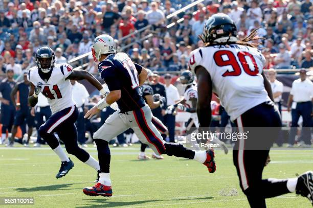 Tom Brady of the New England Patriots is pursued by Zach Cunningham and Jadeveon Clowney of the Houston Texans during the third quarter of a game at...