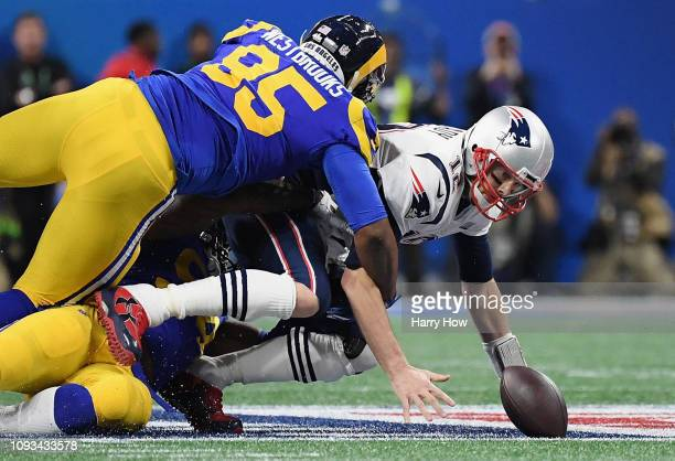 Tom Brady of the New England Patriots is sacked by Aaron Donald and Ethan Westbrooks of the Los Angeles Rams in the first half during Super Bowl LIII...