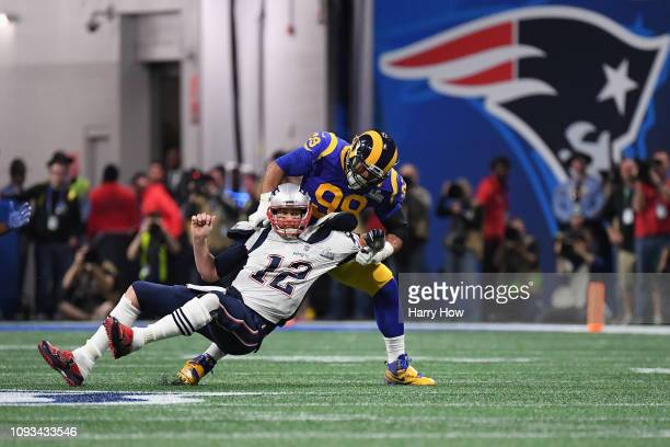 Tom Brady of the New England Patriots is sacked by Aaron Donald of the Los Angeles Rams in the first quarter during Super Bowl LIII at MercedesBenz...
