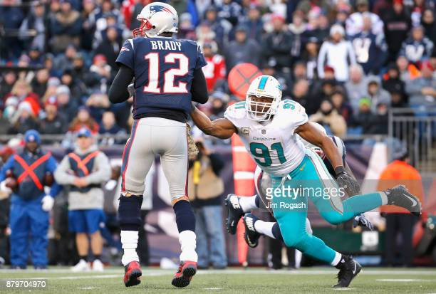 Tom Brady of the New England Patriots is sacked by Cameron Wake of the Miami Dolphins during the fourth quarter of a game at Gillette Stadium on...