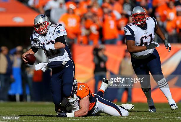 Tom Brady of the New England Patriots is sacked by Derek Wolfe of the Denver Broncos in the first quarter in the AFC Championship game at Sports...