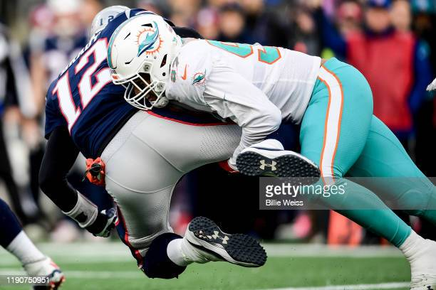 Tom Brady of the New England Patriots is sacked by Trent Harris of the Miami Dolphins during the fourth quarter of a game at Gillette Stadium on...