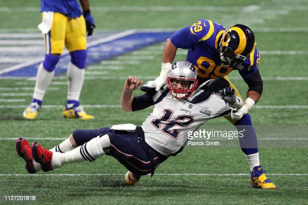 Tom Brady of the New England Patriots is tackled by Aaron Donald of the Los Angeles Rams in the first quarter during Super Bowl LIII at Mercedes-Benz...