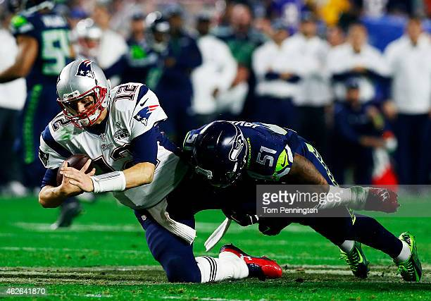 Tom Brady of the New England Patriots is tackled by Bruce Irvin of the Seattle Seahawks in the fourth quarter during Super Bowl XLIX at University of...