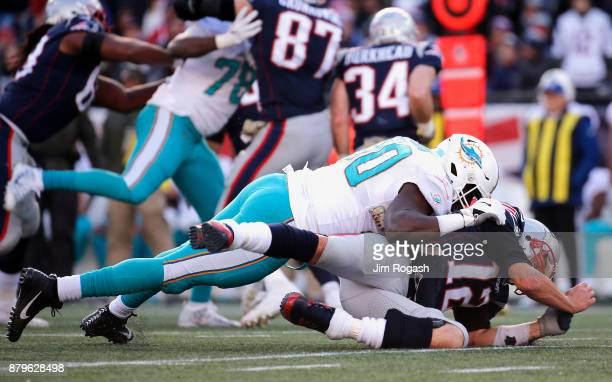 Tom Brady of the New England Patriots is tackled by Charles Harris of the Miami Dolphins during the second quarter of a game at Gillette Stadium on...