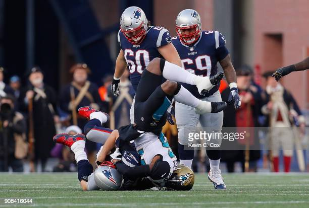 Tom Brady of the New England Patriots is tackled by Dante Fowler of the Jacksonville Jaguars in the second quarter during the AFC Championship Game...
