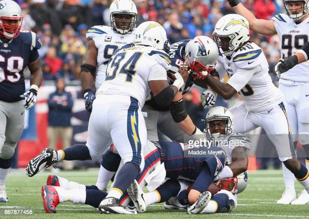 Tom Brady of the New England Patriots is tackled by Desmond King of the Los Angeles Chargers during the third quarter of a game at Gillette Stadium...