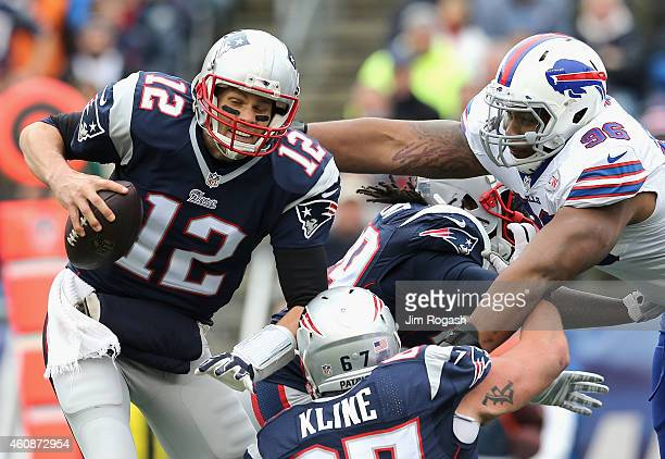 Tom Brady of the New England Patriots is tackled by Stefan Charles of the Buffalo Bills during the second quarter at Gillette Stadium on December 28...