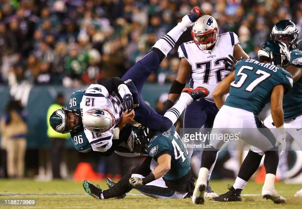 Tom Brady of the New England Patriots is upended by Derek Barnett and Nathan Gerry of the Philadelphia Eagles during the first half at Lincoln...