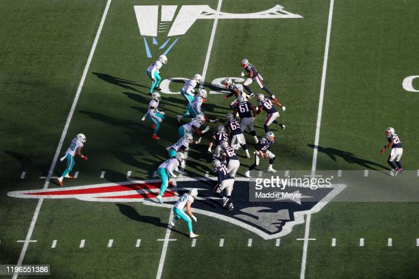 Tom Brady of the New England Patriots looks to hand the ball off to Sony Michel over the Patriots logo during the game against the Miami Dolphins at...