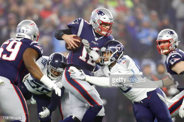 Tom Brady of the New England Patriots looks to pass as he is hit by Harold Landry of the Tennessee Titans in the first quarter of the AFC Wild Card...