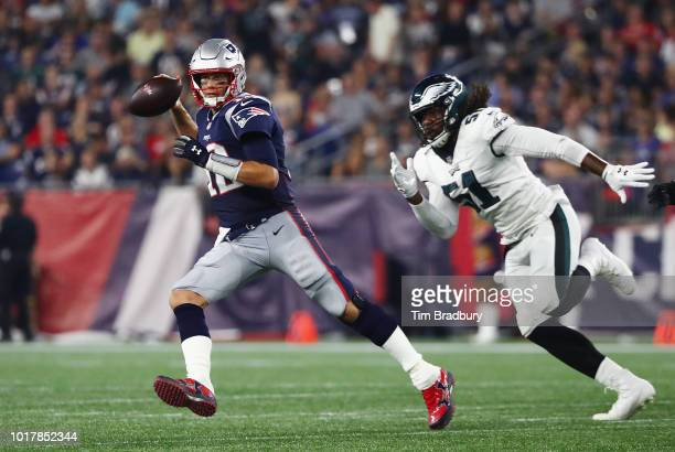 Tom Brady of the New England Patriots looks to pass the ball as he is pursued by Steven Means of the Philadelphia Eagles in the first half during the...