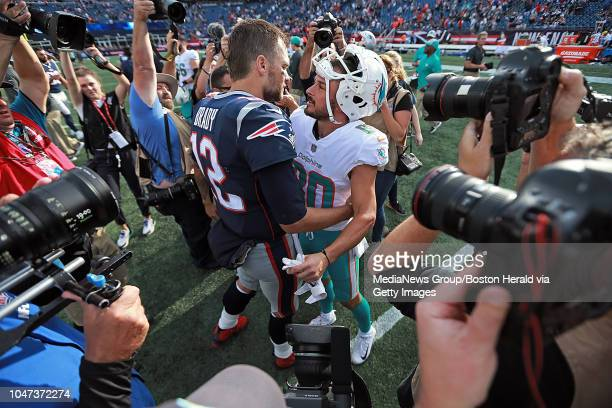 Tom Brady of the New England Patriots meets up with former teammate Danny Amendola of the Miami Dolphins after the NFL game at Gillette Stadium on...