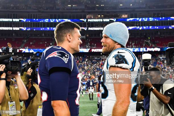 Tom Brady of the New England Patriots meets with Greg Olsen of the Carolina Panthers following the Patriots 10-3 preseason victory at Gillette...