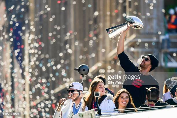 Tom Brady of the New England Patriots reacts as he holds the Vince Lombardi trophy during the Super Bowl Victory Parade on February 05 2019 in Boston...