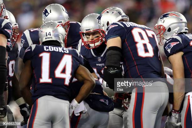 Tom Brady of the New England Patriots reacts in the huddle with Brandin Cooks and Rob Gronkowski during the fourth quarter in the AFC Divisional...