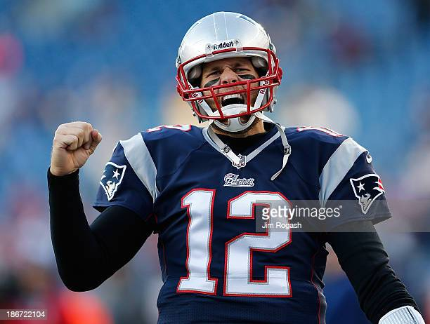 Tom Brady of the New England Patriots reacts to the cheers of fans as he runs onto the field before a game with the Pittsburgh Steelers at Gillette...