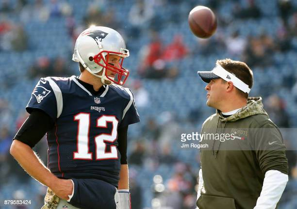 Tom Brady of the New England Patriots reacts with offensive coordinator Josh McDaniels before a game against the Miami Dolphins at Gillette Stadium...