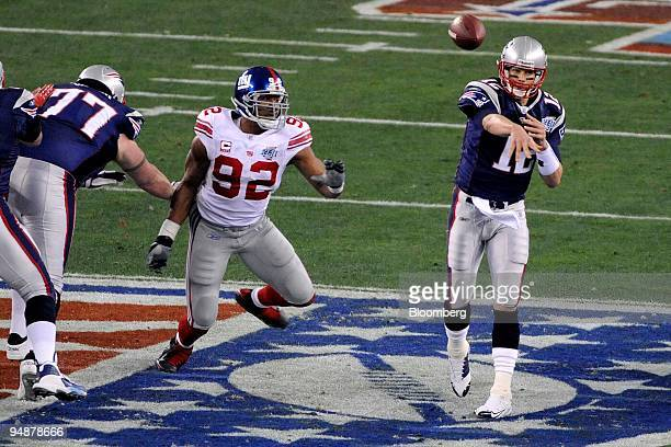 Tom Brady of the New England Patriots right throws a pass under pressure from the Michael Strahan of the New York Giants during the first half of...