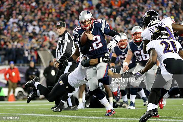 Tom Brady of the New England Patriots runs in for a touchdown in the first quarter against the Baltimore Ravens during the 2014 AFC Divisional...