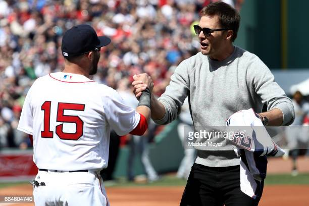 Tom Brady of the New England Patriots shakes hands with Dustin Pedroia of the Boston Red Sox after throwing out the first pitch before the opening...