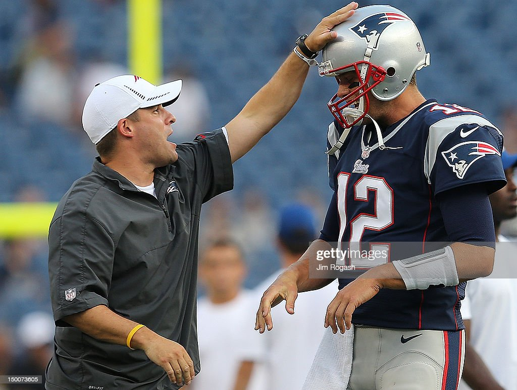 Tom Brady #12 of the New England Patriots shares a moment with Offensive Coordinator Josh McDaniels before a preseason game with New Orleans Saints at Gillette Stadium on August 9, 2012 in Foxboro, Massachusetts.