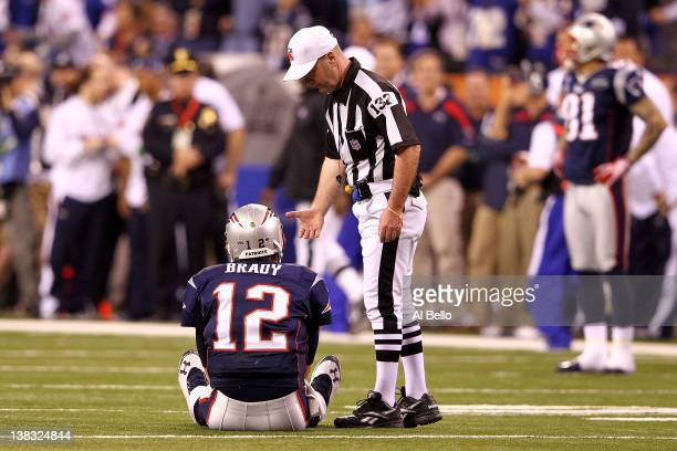 Tom Brady of the New England Patriots sits on the ground after throwing an interception to Chase Blackburn of the New York Giants over Rob Gronkowski...
