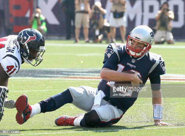 Tom Brady of the New England Patriots slides as he is tackled by Zach Cunningham of the Houston Texans during the second quarter of a game at...
