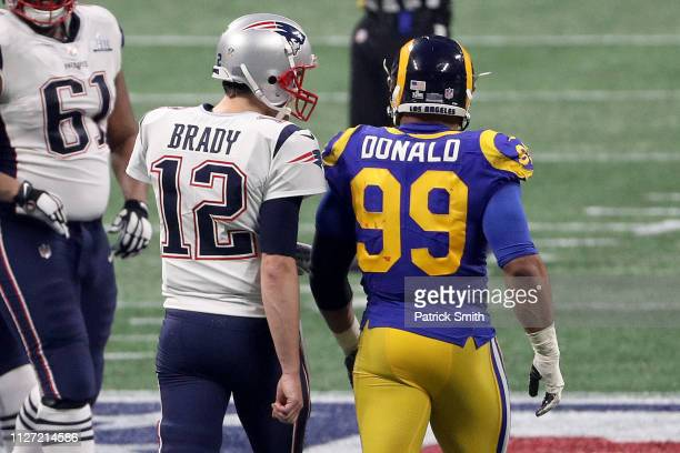 Tom Brady of the New England Patriots speaks to Aaron Donald of the Los Angeles Rams in the fourth quarter during Super Bowl LIII at Mercedes-Benz...