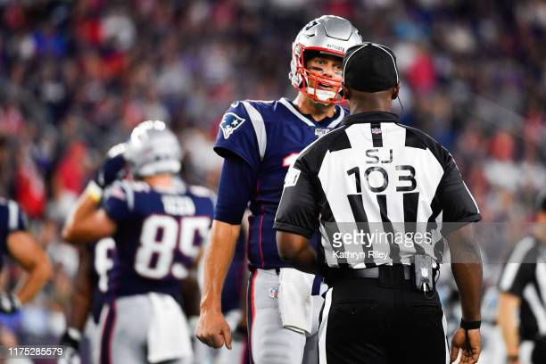 Tom Brady of the New England Patriots speaks with side judge Eugene Hall during the first quarter of a preseason game against the Carolina Panthers...