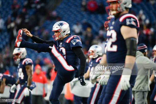 Tom Brady of the New England Patriots stretches during warmups prior to the start of the game against the Kansas City Chiefs at Gillette Stadium on...
