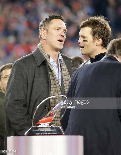 Tom Brady of the New England Patriots talks with Drew Bledsoe during the Lamar Hunt trophy presentation after the AFC Championship Game against the...