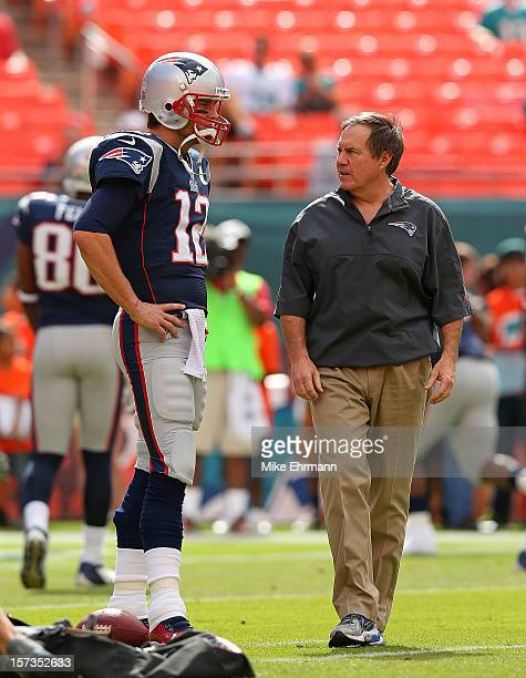 Tom Brady of the New England Patriots talks with head coach Bill Belichick during a game against the Miami Dolphins at Sun Life Stadium on December 2...