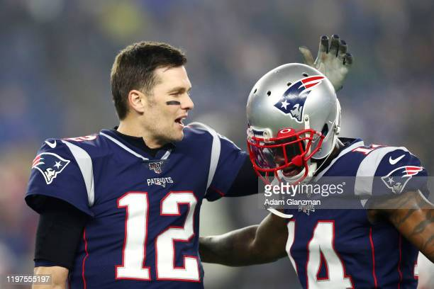 Tom Brady of the New England Patriots talks with teammate Mohamed Sanu before the AFC Wild Card Playoff game against the Tennessee Titans at Gillette...