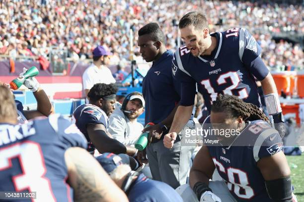 Tom Brady of the New England Patriots talks with teammates on the sideline during the second half against the Miami Dolphins at Gillette Stadium on...