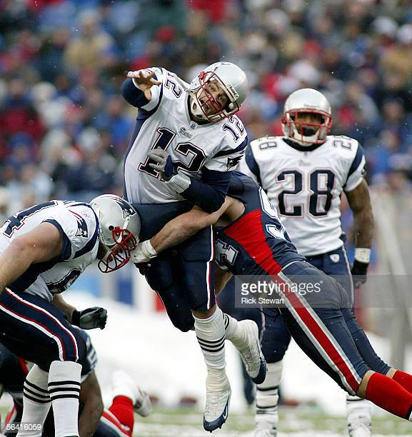 Tom Brady of the New England Patriots throws a pass as heis hit by Aaron Schobel of the Buffalo Bills on December 11 2005 at Ralph Wilson Stadium in...
