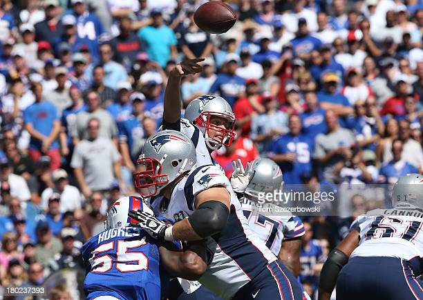 Tom Brady of the New England Patriots throws a pass as Sebastian Vollmer blocks Jerry Hughes of the Buffalo Bills during NFL game action at Ralph...