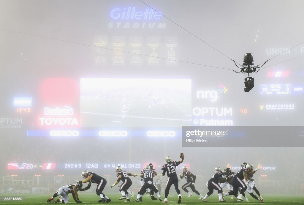 Tom Brady #12 of the New England Patriots throws as fog falls on the field during the fourth quarter of a game against the Atlanta Falcons at Gillette Stadium on October 22, 2017 in Foxboro, Massachusetts.
