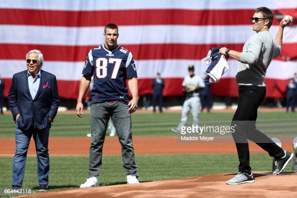 Tom Brady of the New England Patriots throws out the first pitch as Patriots owner Robert Kraft and Rob Gronkowski look on before the opening day...