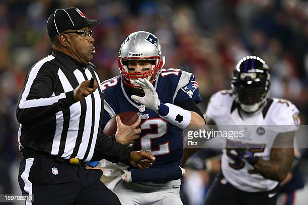 Tom Brady of the New England Patriots tries to avoid umpire Chad Brown during a run against the Baltimore Ravens during the 2013 AFC Championship...
