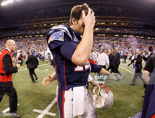 Tom Brady of the New England Patriots walks off the field after losing to the New York Giants by a score of 2117 in Super Bowl XLVI at Lucas Oil...